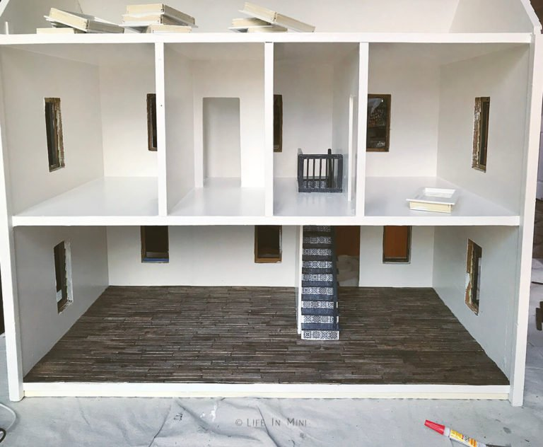 Inside an empty dollhouse, painted white, with downstairs having dark wooden floors and miniature staircase in