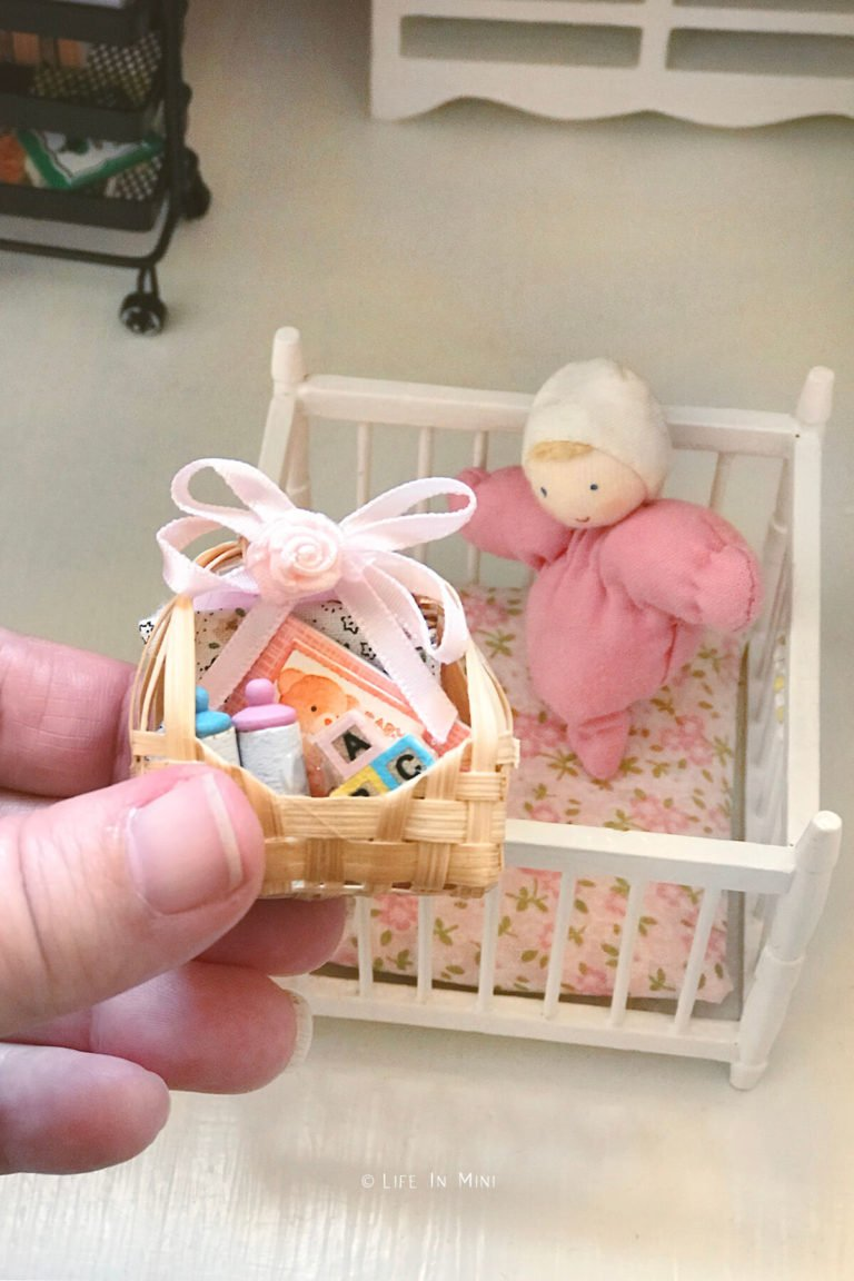 Miniature basket with baby things inside of it and miniature playpen with mini baby