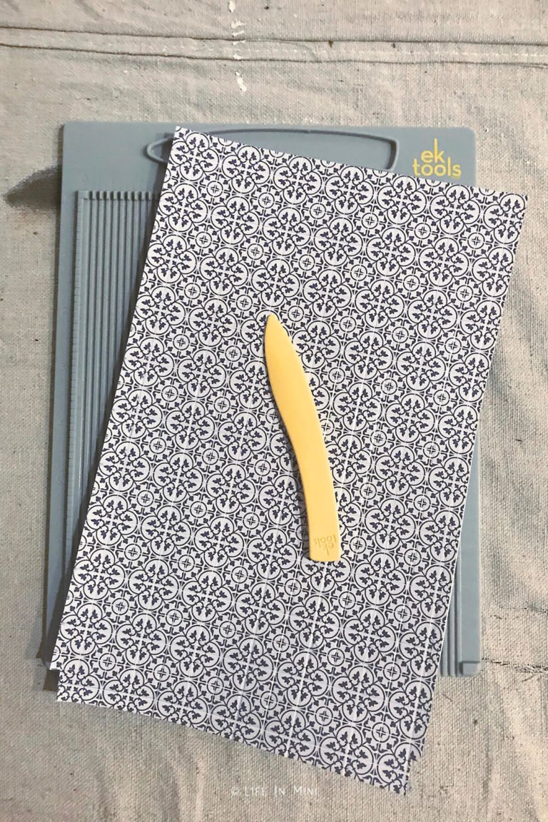 Using a scoring pad and stylus to score tile printed onto photo paper to mimic grout lines for dollhouse bathroom flooring