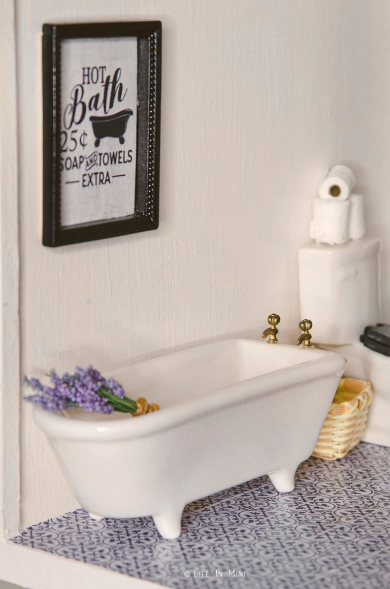 Miniature bathtub in dollhouse with framed mini artwork on the wall