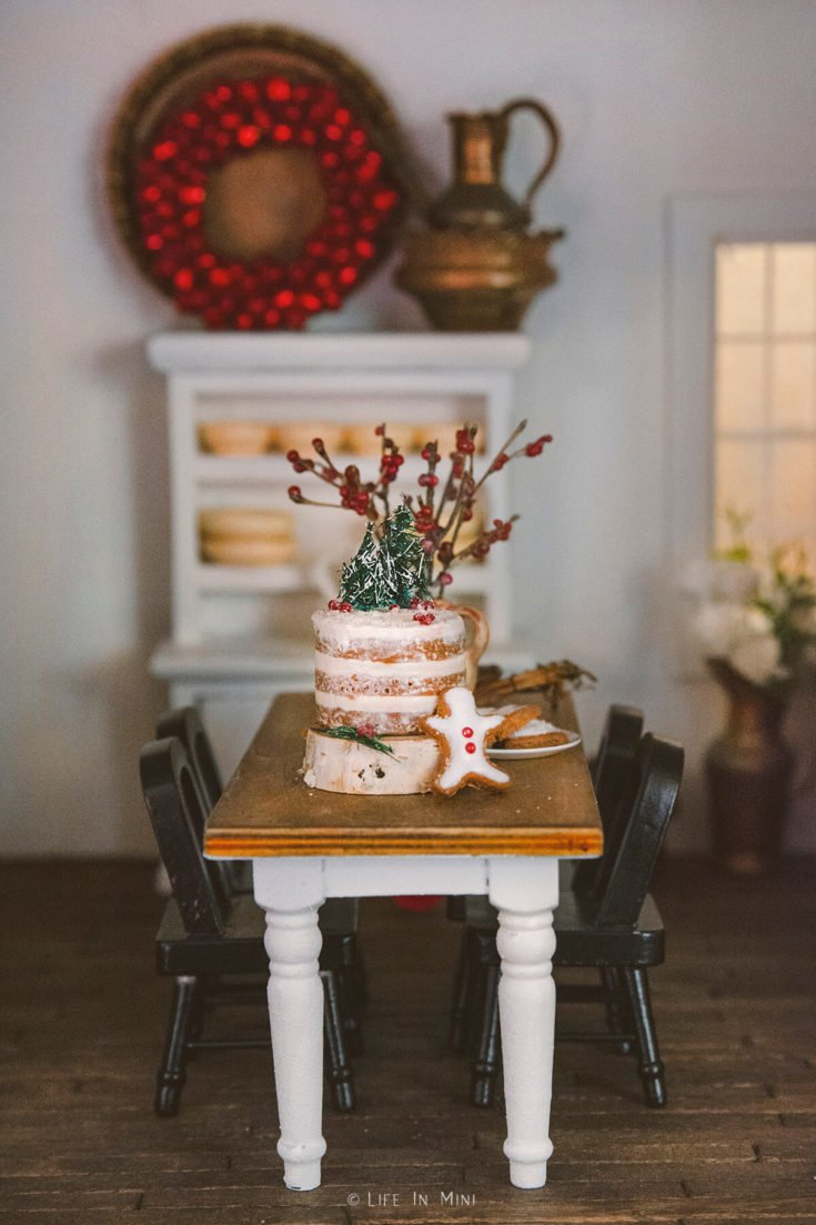 Dollhouse farmhouse dining table with a cake on it with dark wooden flooring
