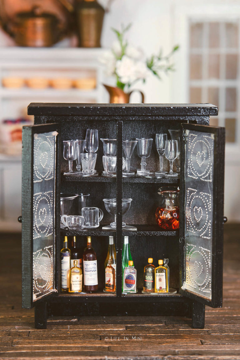 A black and metal miniature cupboard open with mini stemware and bottles inside