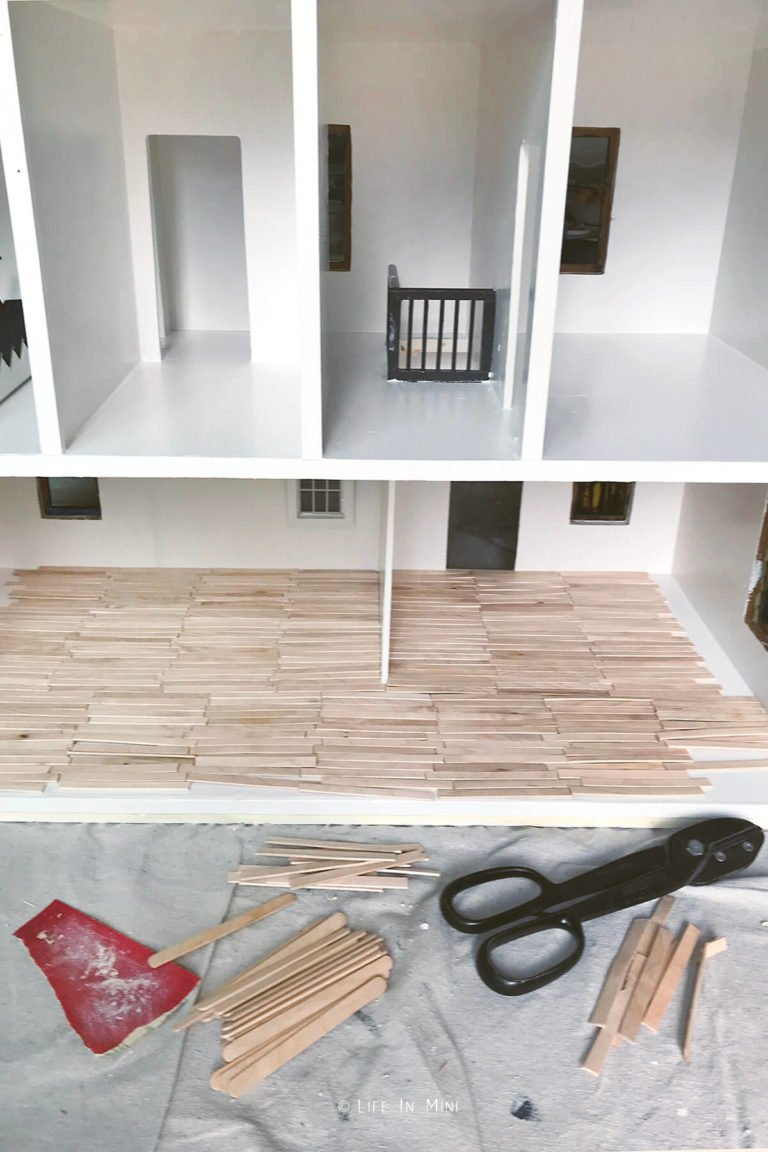Wooden popsicle sticks cut and laid out in dollhouse
