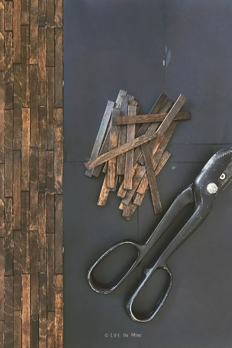 Gluing down stained popsicle sticks onto cardstock