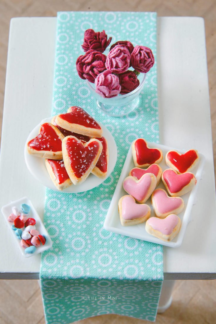 Miniature valentine heart cookies made with polymer clay on a dollhouse table
