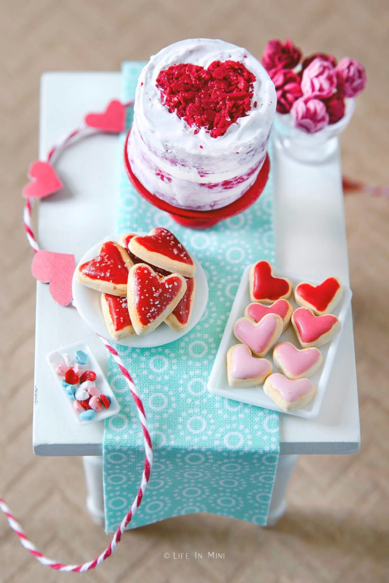 Top view of a miniature white table with mini valentine heart cookies and mini red velvet cake