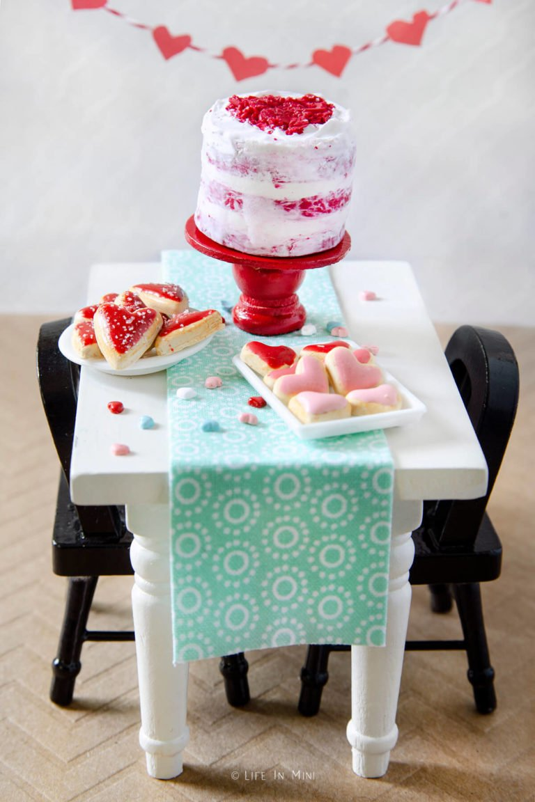 Side view of a miniature white table with mini valentine heart cookies and mini red velvet cake