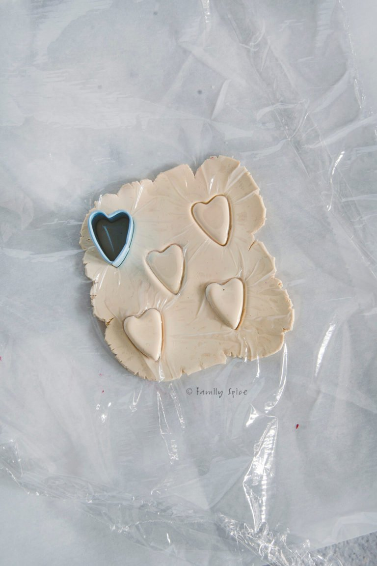 Cutting out miniature hearts over plastic wrap covered polymer clay