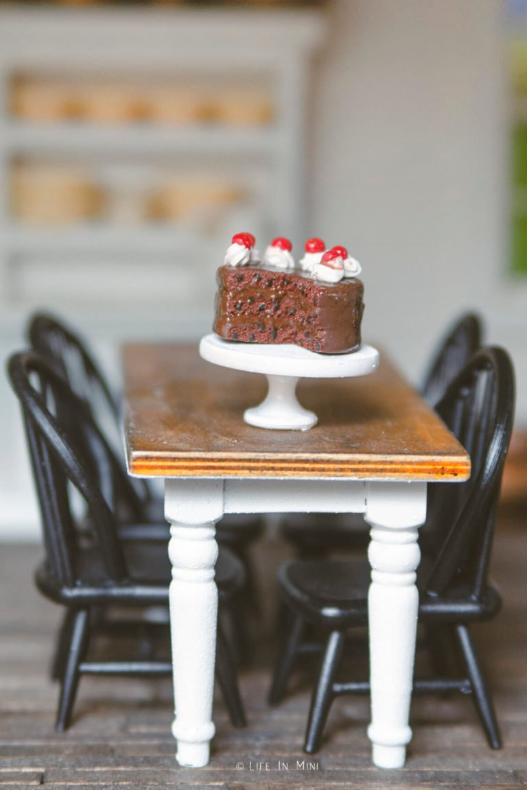 A miniature chocolate cake on a mini white cake stand