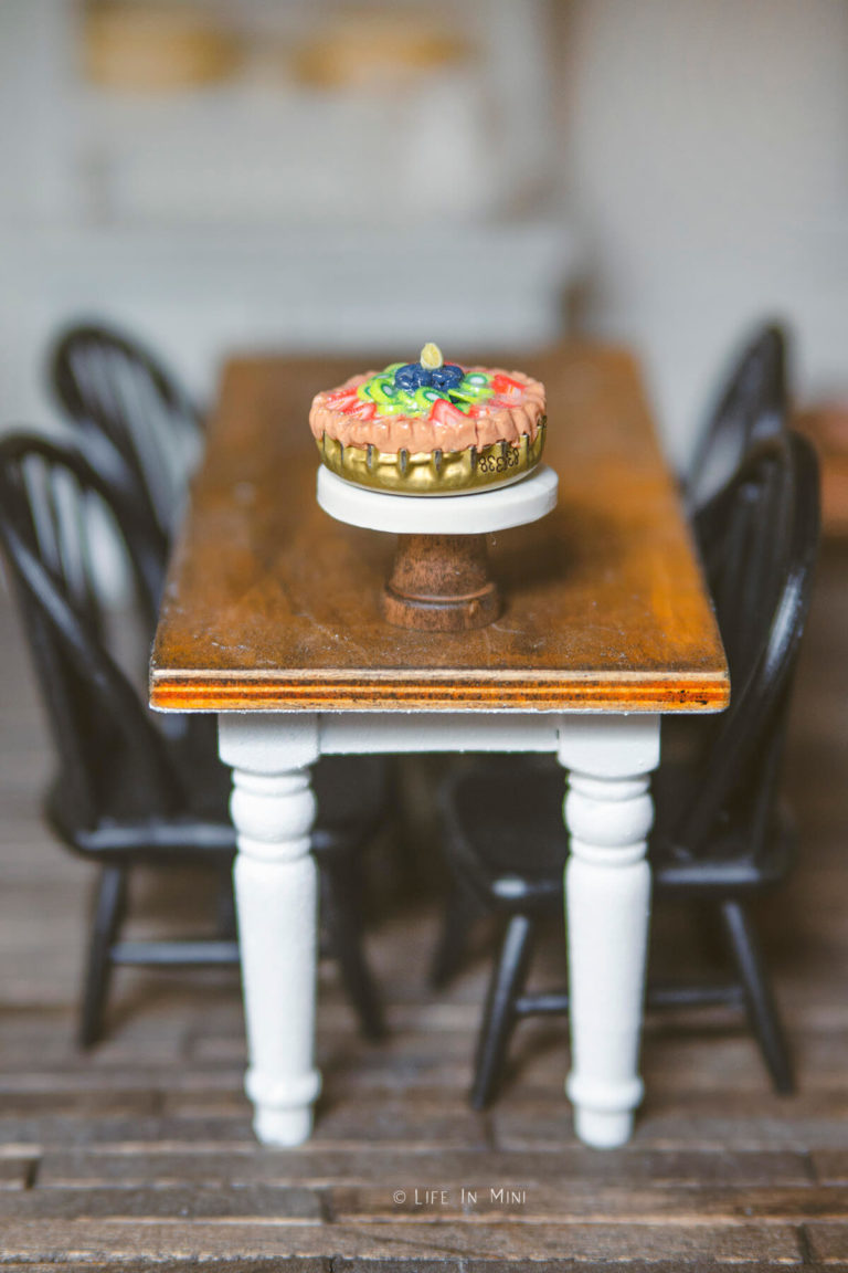 A miniature pie on a miniature cake stand