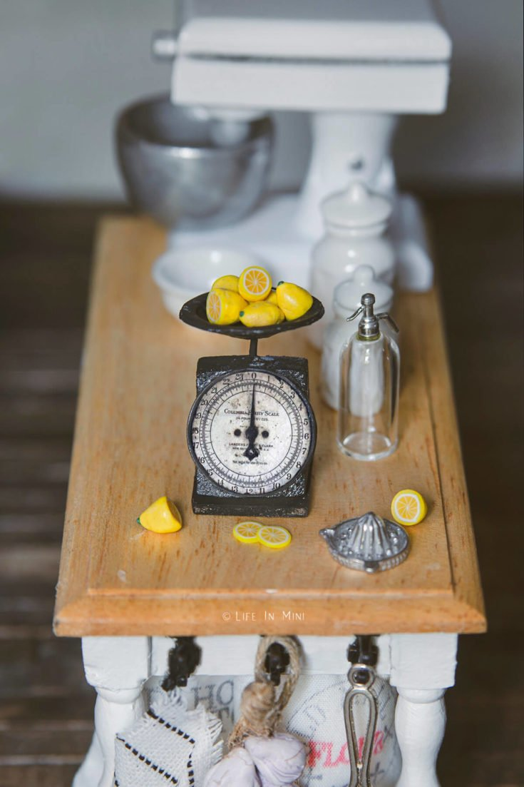 A miniature antique kitchen scale in a dollhouse kitchen table