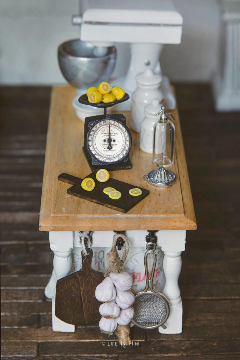 A miniature antique kitchen scale with lemons on it with a mini dollhouse wood cutting board and lemon slices on it