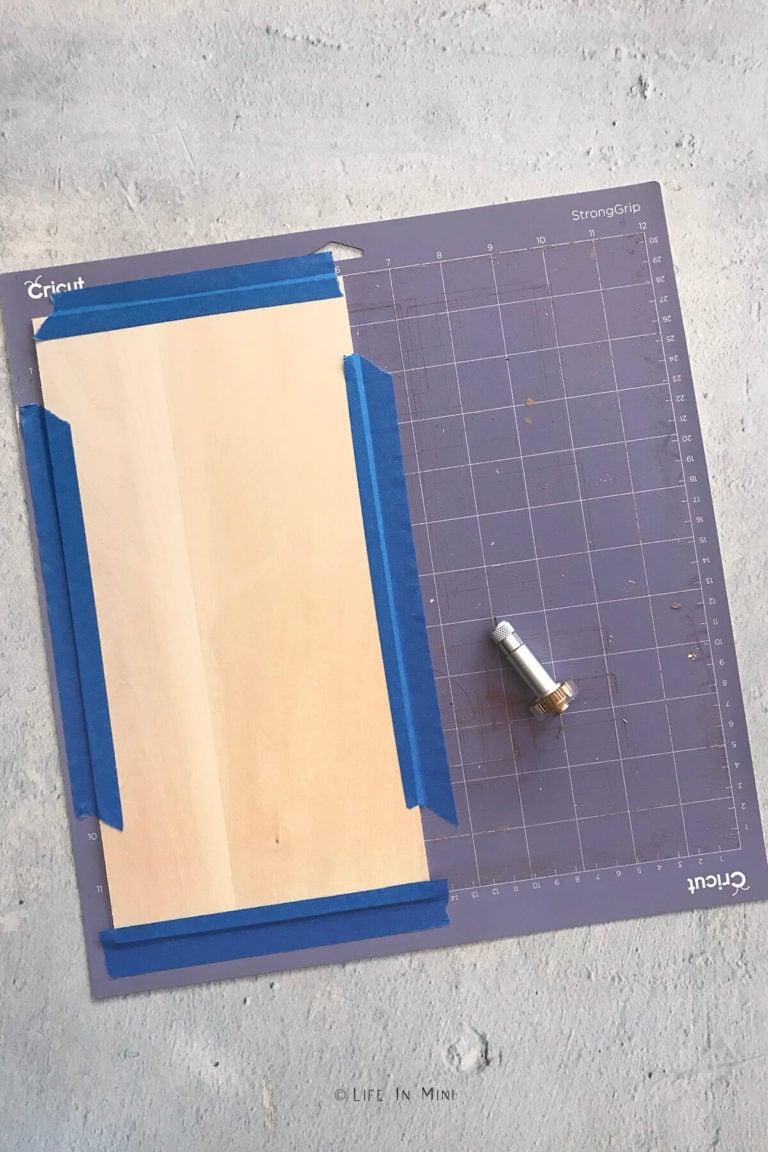 A sheet of basswood taped onto a purple Cricut cutting mat