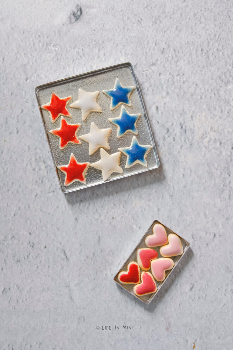 Top view of two small metal pans with miniature cookies in them