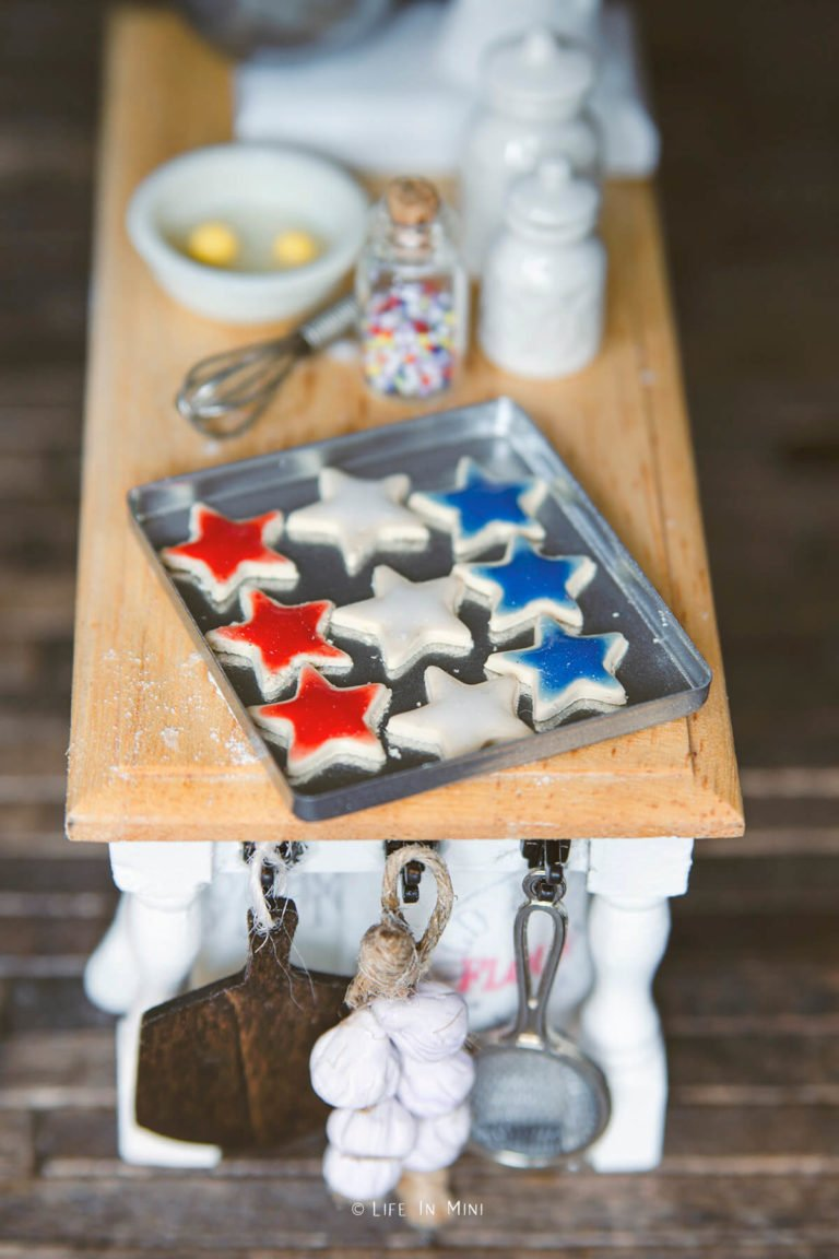 A large miniature cookie sheet with star cookies on a dollhouse kitchen island