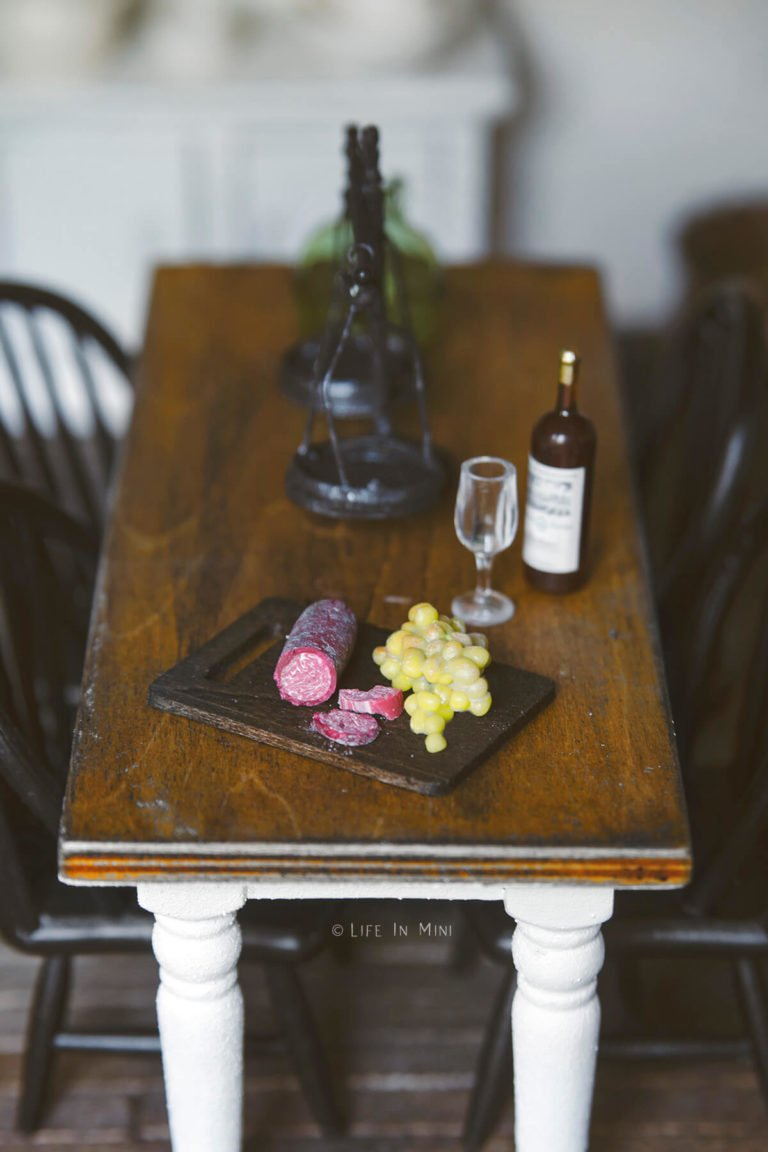Miniature rectangular wood cutting board with a log of mini salami and grapes on it sitting on a dollhouse table