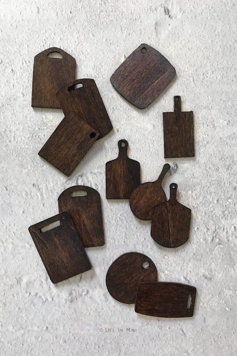 Miniature wood cutting boards of various shapes and sizes stained dark brown