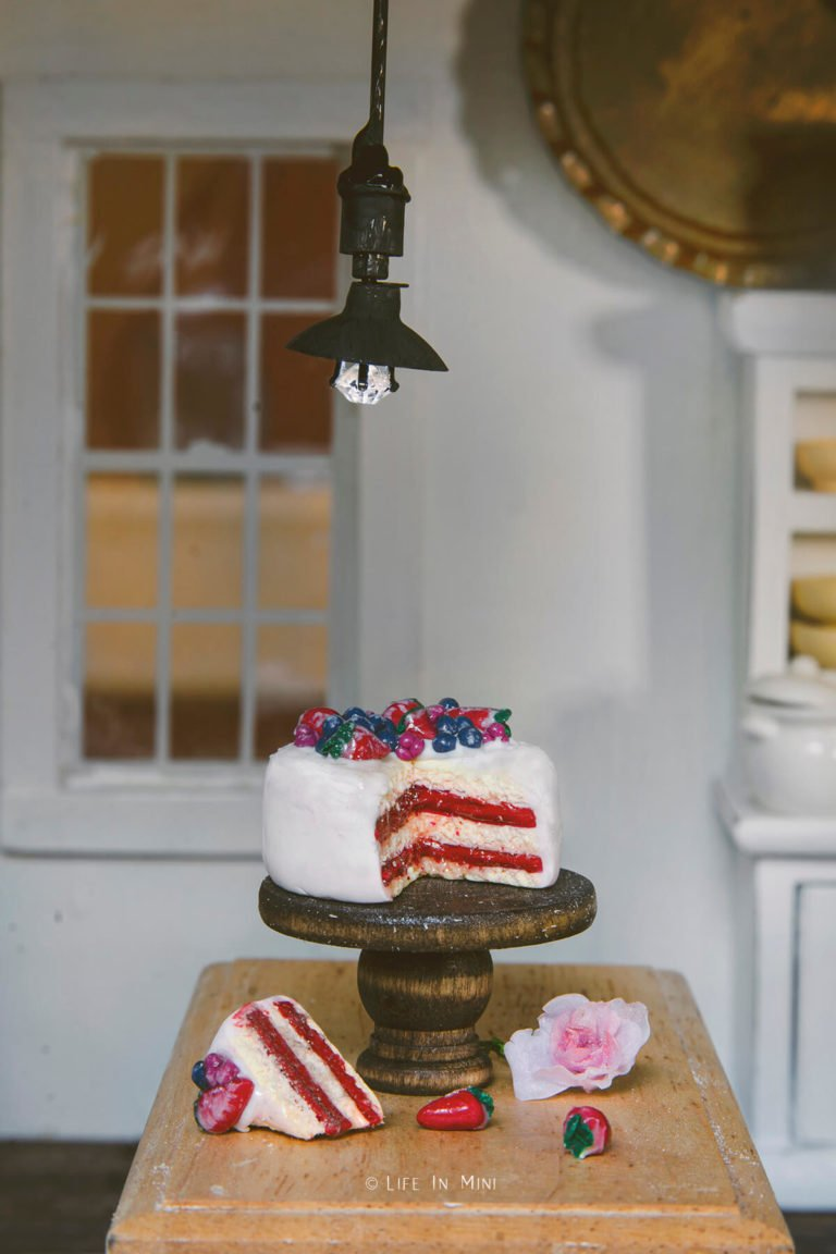 A miniature farmhouse pendant light hanging over a kitchen table with a mini cake on a cake stand