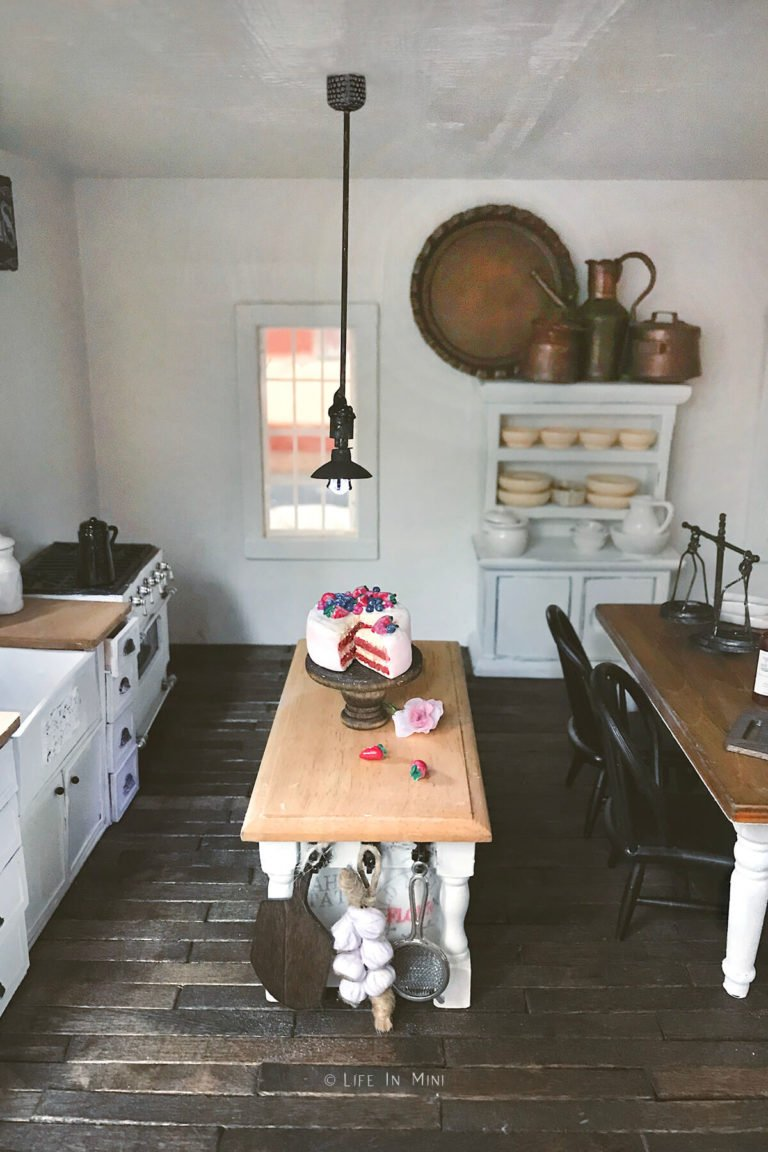 Dollhouse kitchen with a small miniature pendant light hanging over a kitchen table with a mini cake on it