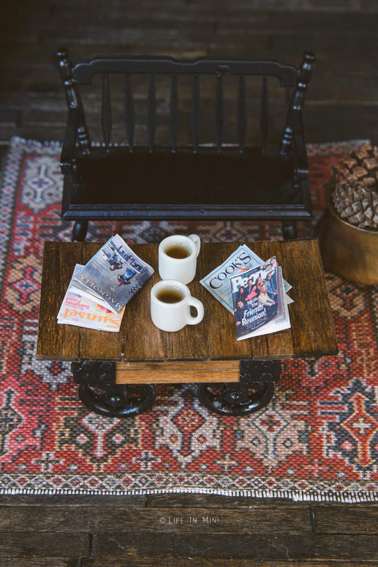 Top view of a miniature black bench next to a rustic coffee table with two coffee mugs and four mini magazines