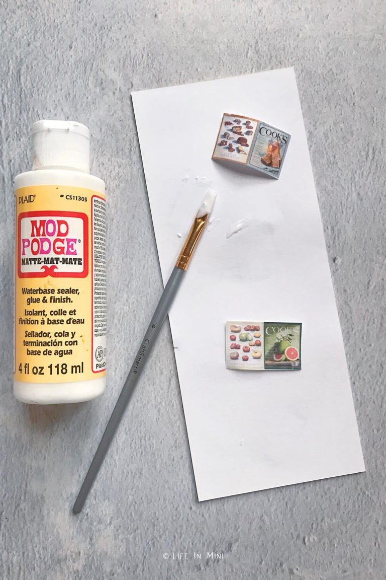 A bottle of Mod Podge with a paint brush and print outs of mini magazines