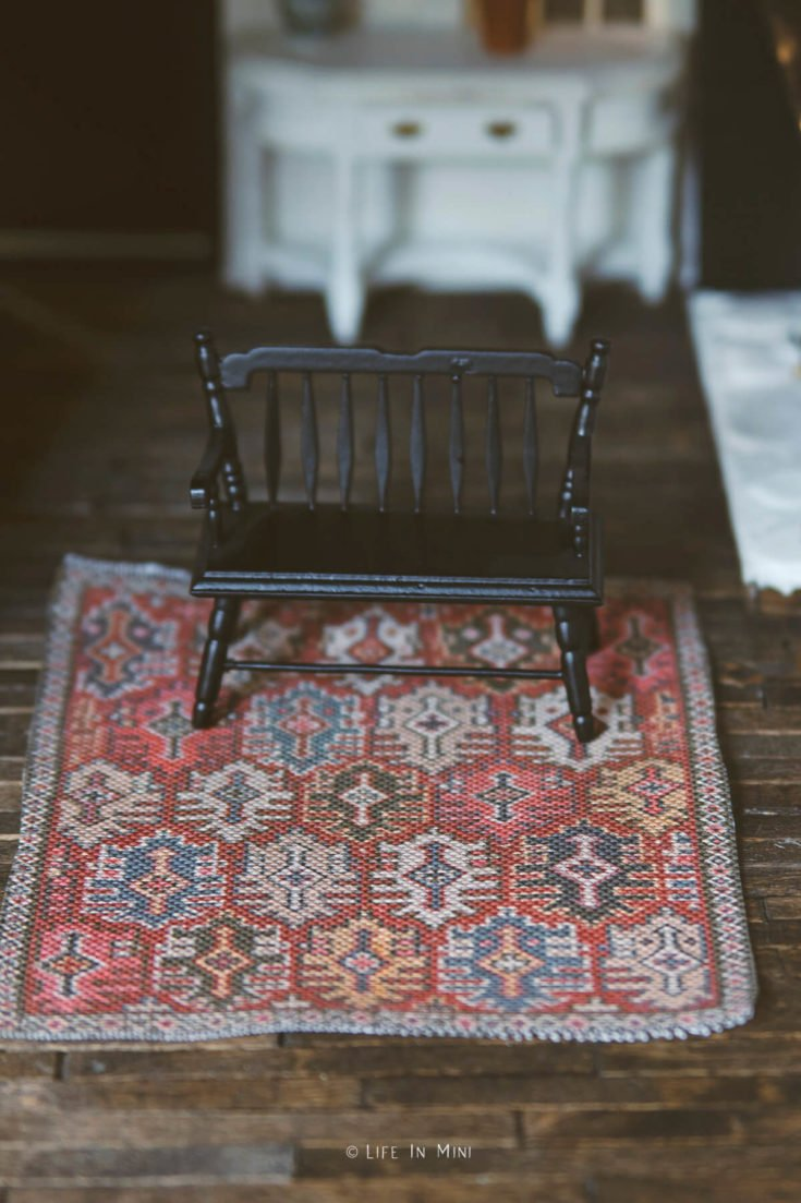 A dollhouse den with dark wooden floors, red rug and black wooden bench