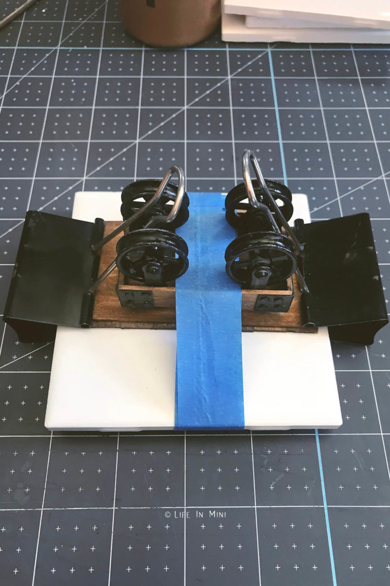 A dollhouse coffee table assembled, clipped and taped to a tile