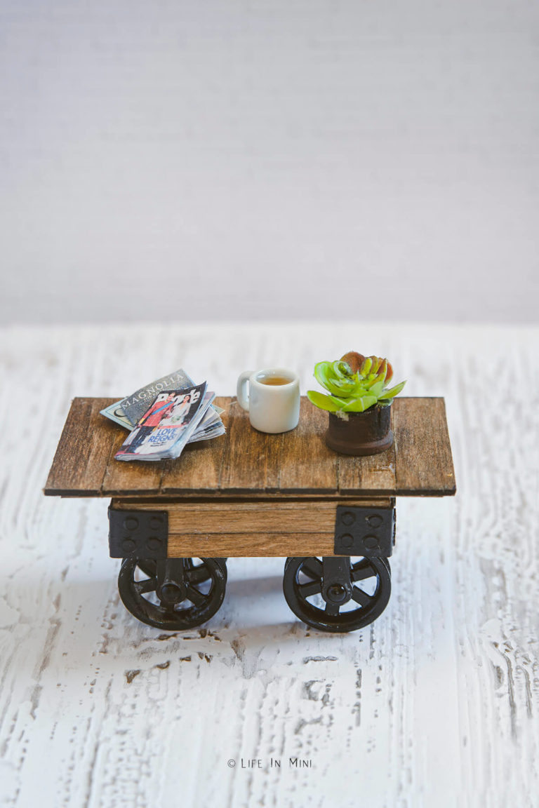 A miniature farmhouse coffee table with pulley wheels on a white background