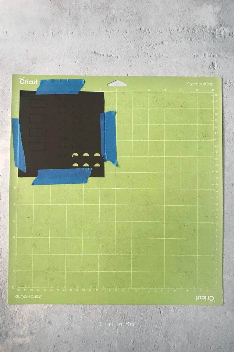 A small square piece of black kraftboard secured on a cricut mat