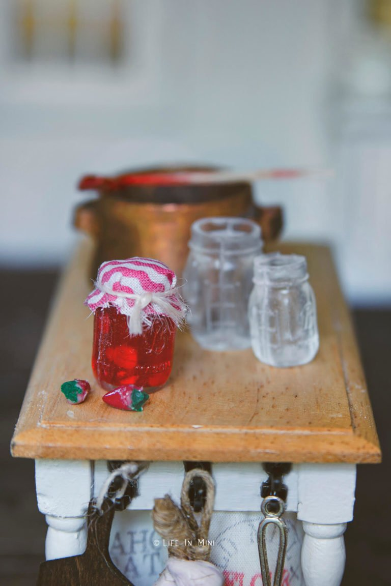 A miniature jar with strawberry jam made with uv resin in a dollhouse kitchen