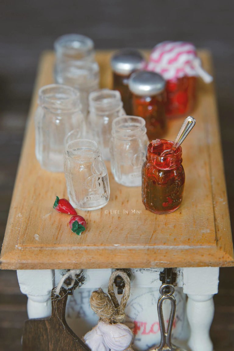 Assorted empty miniature mason jars in a dollhouse kitchen with mini jars of strawberry jam