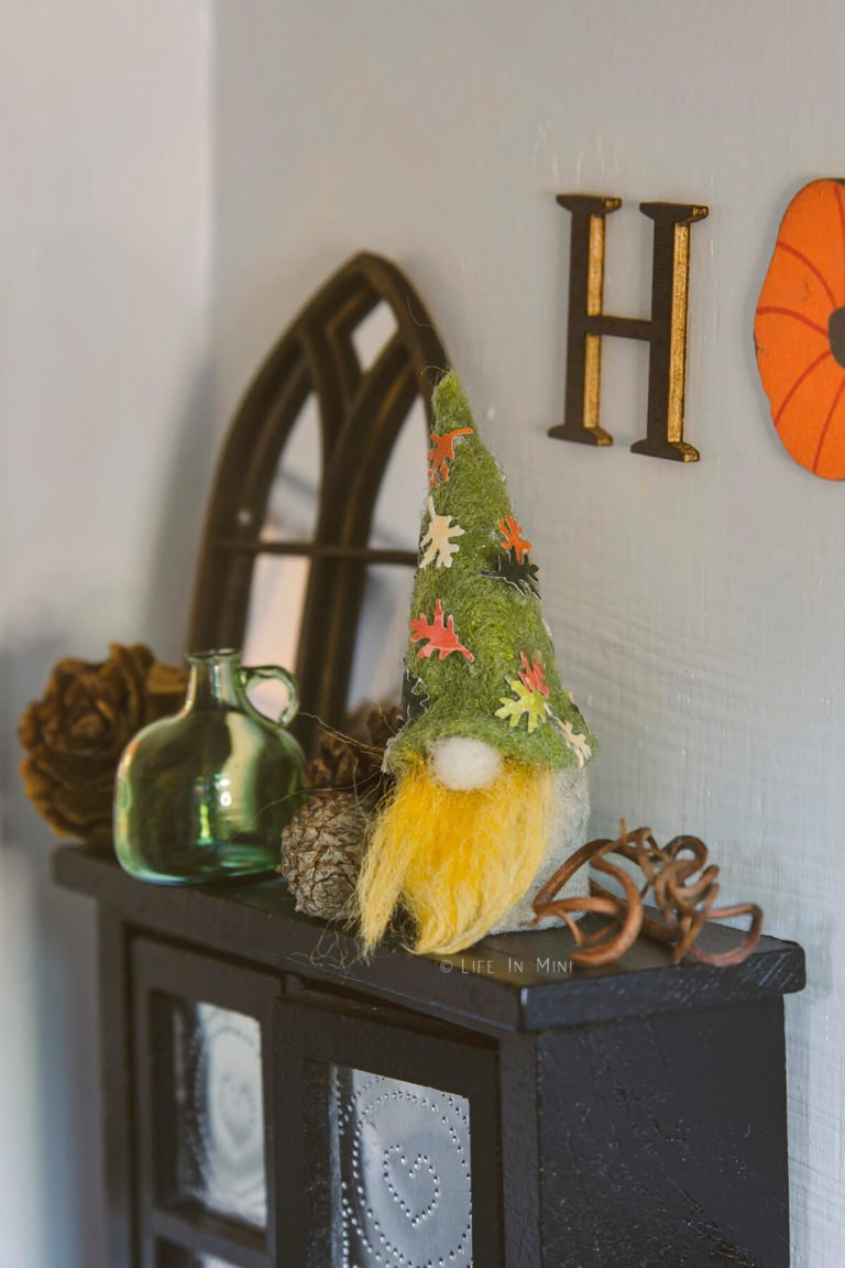 A miniature gnome decorated in fall colors with leaves on its hat on a mantle with other fall decor