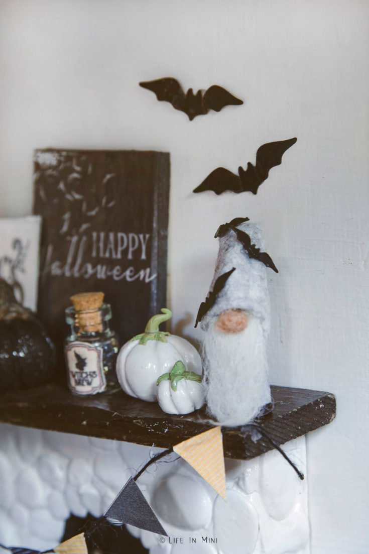 Closeup of a grey miniature gnome with bats on a dollhouse fireplace mantle with other halloween decorations