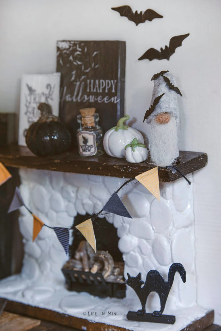 A dollhouse fireplace decorated with various black and white halloween decorations