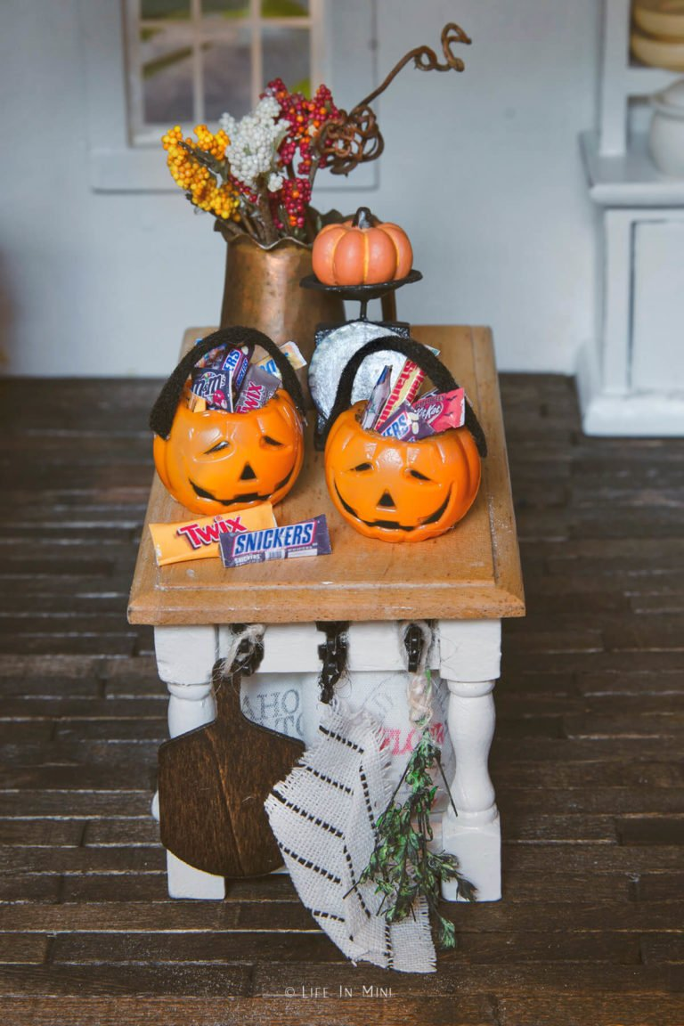 Two miniature plastic pumpkin pails filled with mini candies in a dollhouse kitchen
