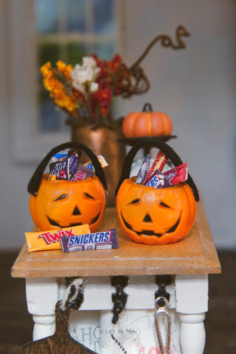 Closeup of miniature plastic pumpkin pails filled with mini candies in a dollhouse kitchen