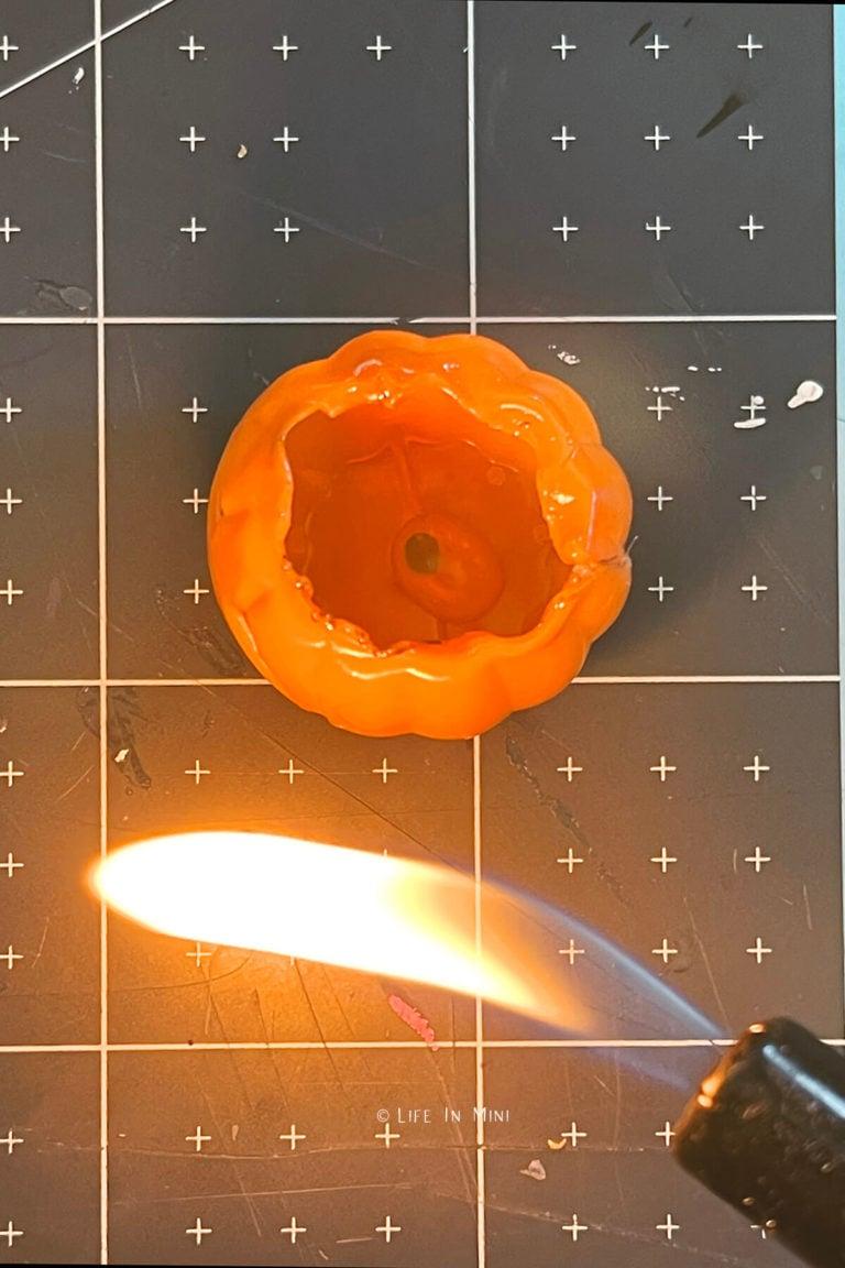 A lighter flame melting edges of plastic pumpkins