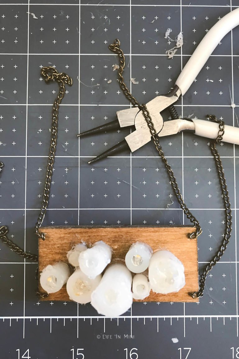 Chains secured to the wooden box of a miniature chandelier with candles