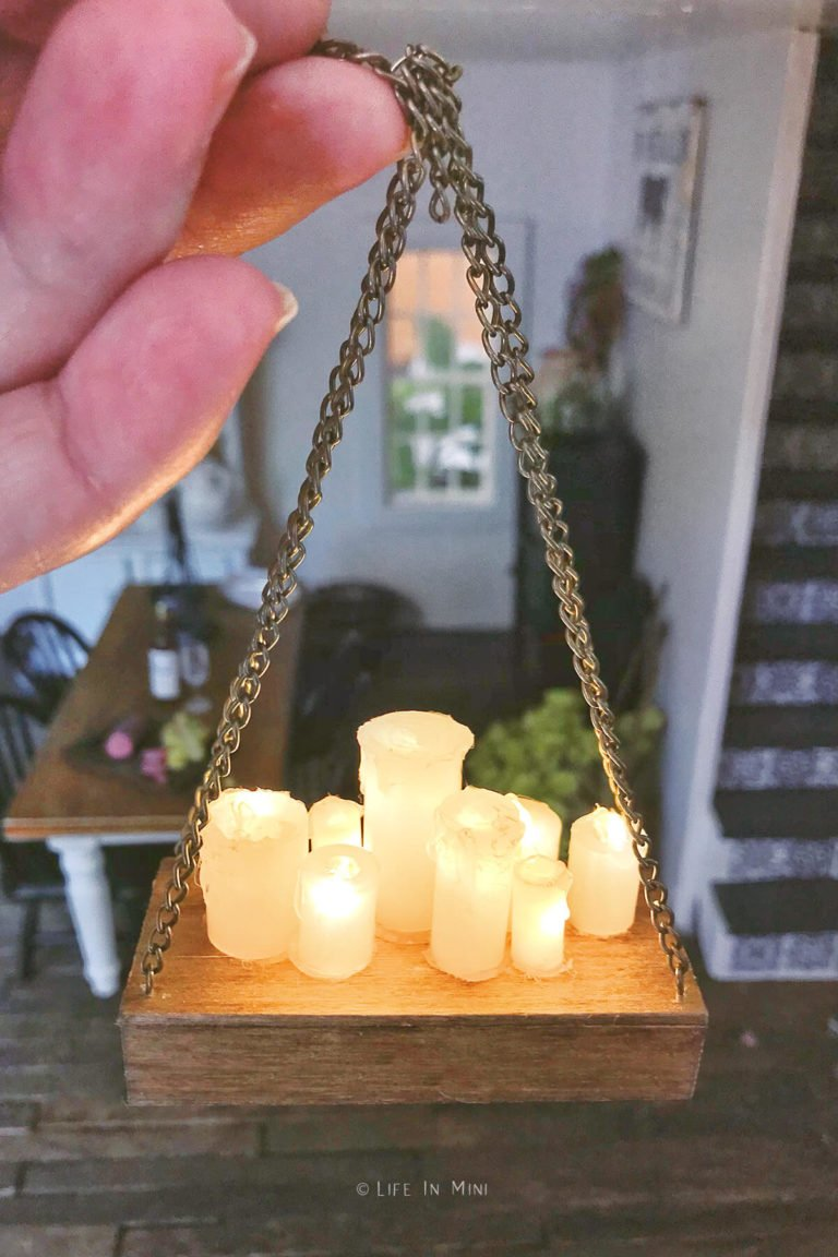 A hand holding up a battery operated dollhouse chandelier