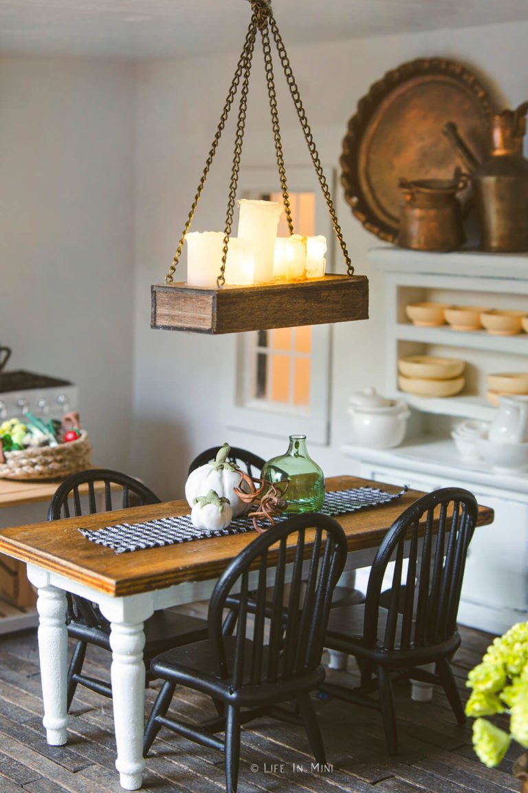 A rustic candle dollhouse chandelier hanging over a dining table in a dollhouse