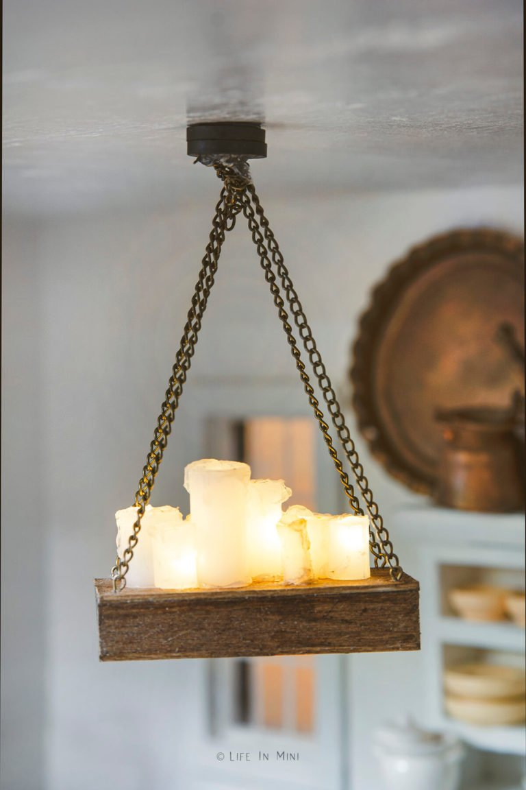 Closeup of a battery operated miniature chandelier hanging in a dollhouse