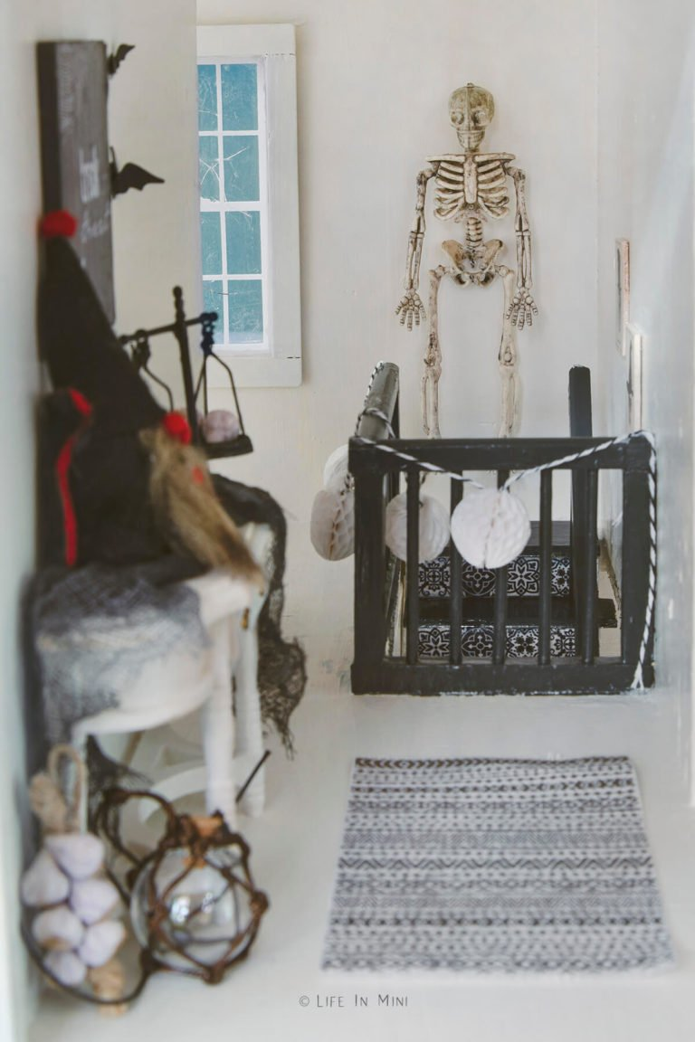 Upstairs hallway in a dollhouse decorated with mini halloween decorations including a skeleton