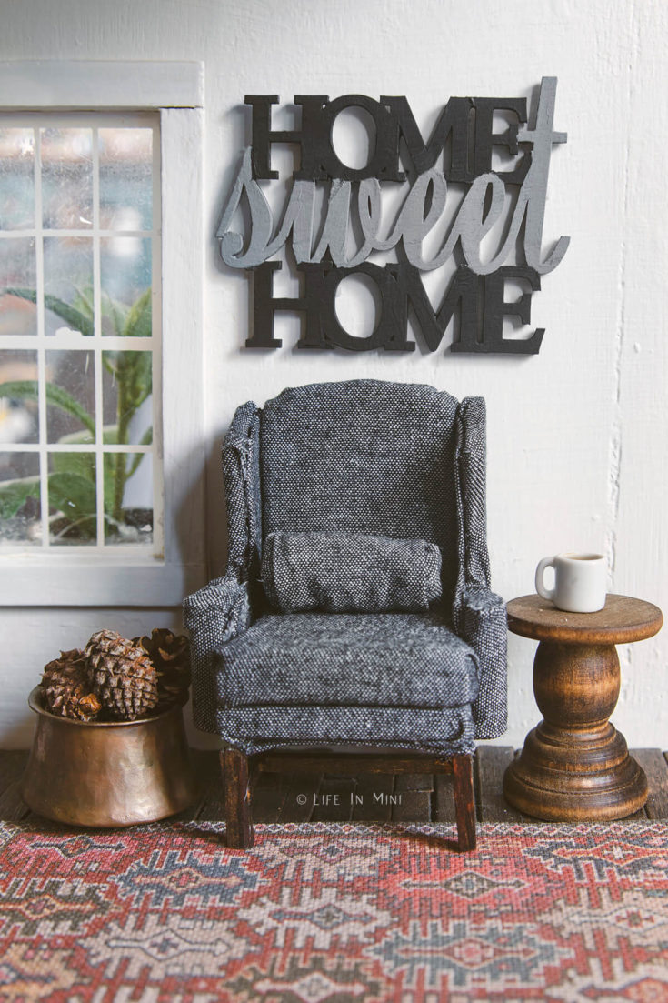 Miniature charcoal wing chair on a rug with a side table and a 'home sweet home' sign over it