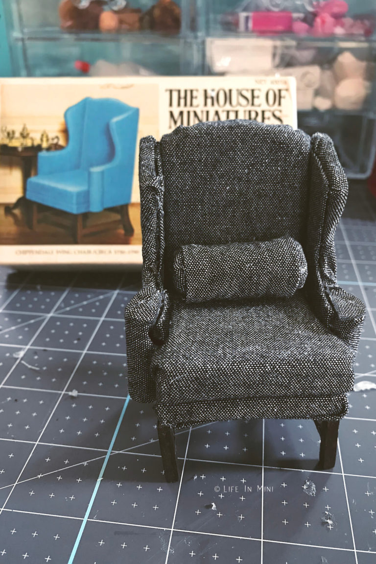 A miniature upholstered grey wing chair from The House of Miniatures kit