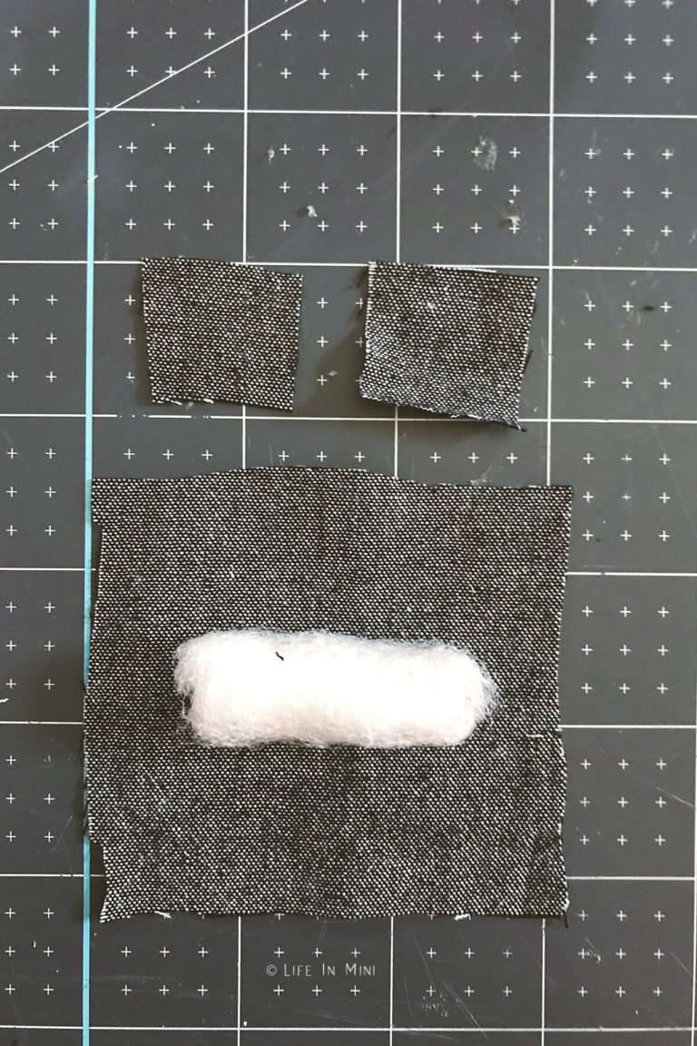 A tube covered in batting laying on a piece of fabric